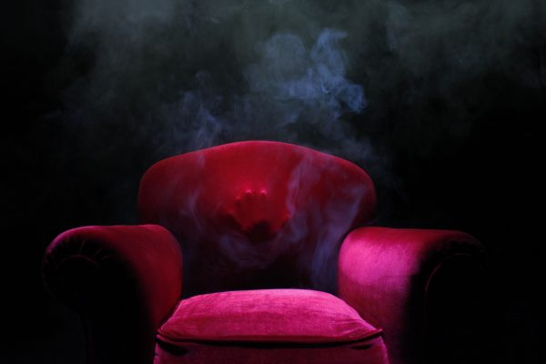 A large red arm chair in dark lighting appears to have someone inside it as a hand is pressed against the material of the back of the seat.
